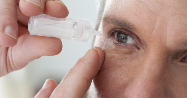 A man using eye drops