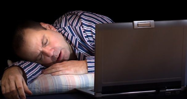 a man asleep in front of a computer